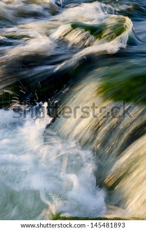 Small waterfalls in a fast moving river with golden light reflecting the sunset. - stock photo