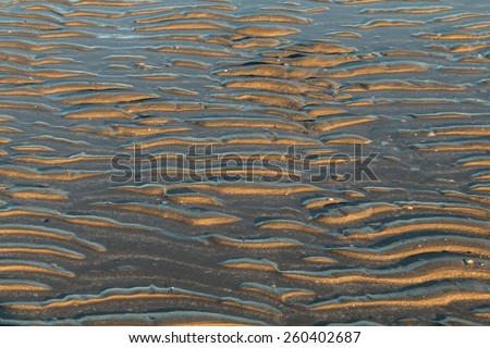 Small wave ripples in the wet sand at low tide - stock photo