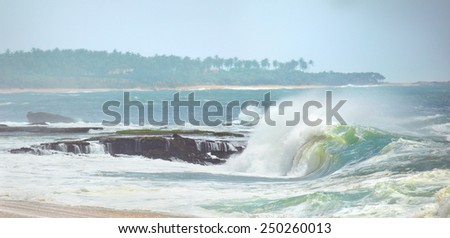 Small waves on the background of a tropical island's shore - stock photo