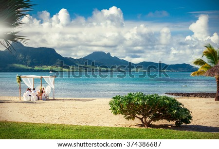 Small wedding group at a tropical beach with lush greenery - stock photo