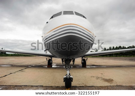 Small white airplane parked at the airport, front view - stock photo