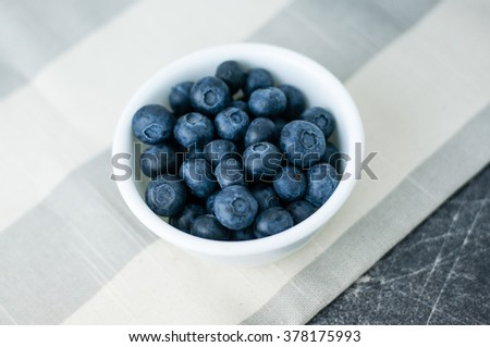 Small white bowl of blueberries on linen tablecloth close up, top view - stock photo