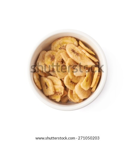 Small white ceramic bowl filled with the dried banana slices, composition isolated over the white background - stock photo