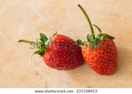 Small white filled with succulent juicy fresh ripe red strawberries on an old wooden - stock photo