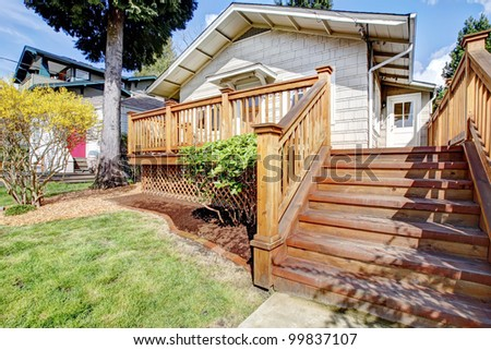 Small white house with wood deck and steps. - stock photo