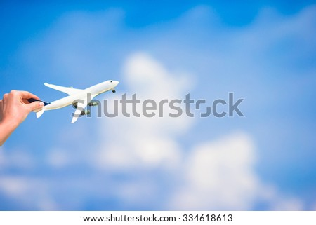 Small white miniature of an airplane on background of blue sky - stock photo