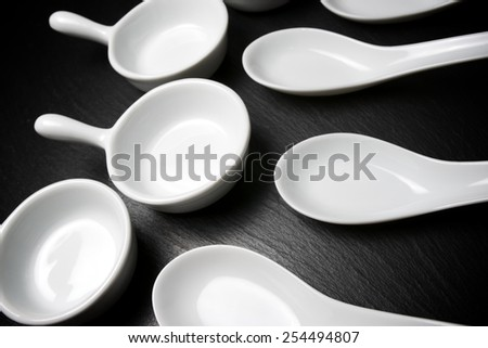 Small white spoons on a table slate - stock photo