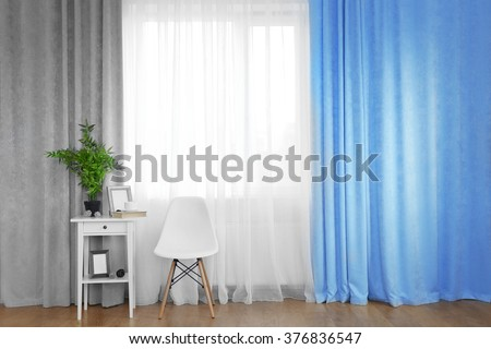 Small white table with green plant and chair on curtain background - stock photo
