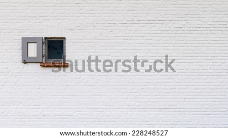 Small window on white wall, minimalistic with copy space - stock photo