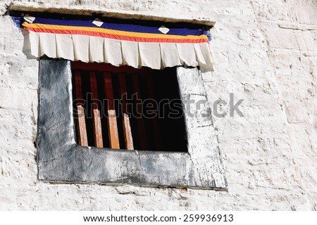 Small window with cross-arms on the white washed wall of the 1416 AD.founded Drepung monastery of the Gelugpa-Yellow Hat order at the foot of mount Ghephel. Lhasa pref.-Tibet A.R.-China. - stock photo