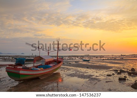 Small wooden boat with light bulbs for night squid fishing on the shore during ebb tide, Thailand - stock photo
