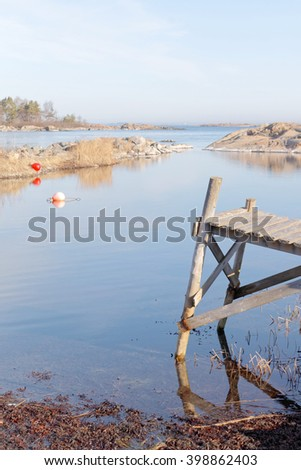 Small wooden bridge, coast and islands a sunny day during spring time in scandinavia - stock photo