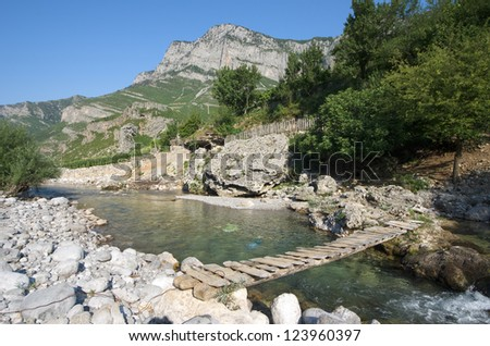 small wooden bridge on a tributary creek of Cemi River in Commune Kelmend, Albania - stock photo