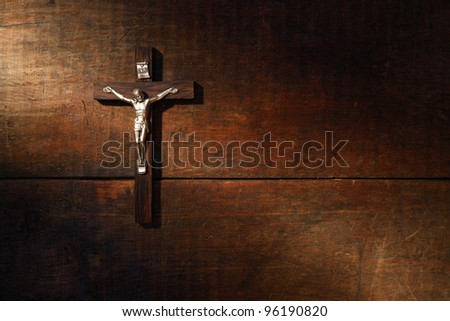 Small wooden crucifix hanging on wooden surface under beam of light - stock photo