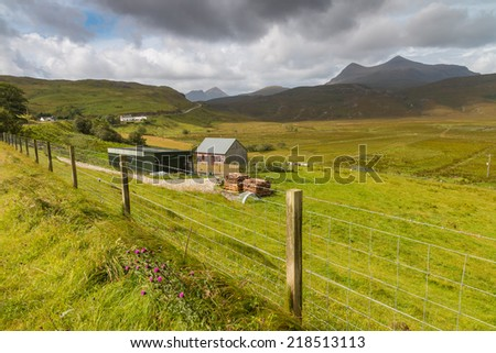 Small wooden farm house between lush green meadown in the Highlands of Scotland - stock photo
