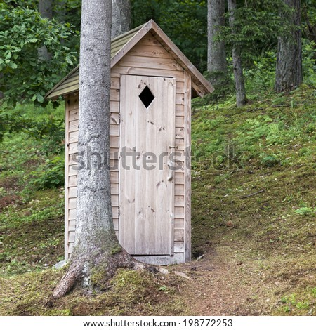 Small wooden outdoors toilet in the forest  - stock photo