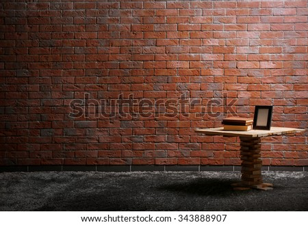 Small wooden table, books and a photo frame on red brick wall background - stock photo