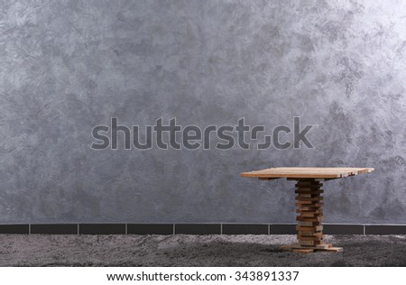 Small wooden table on grey wall background - stock photo
