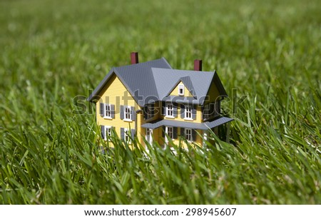 Small yellow house on green grass  - stock photo