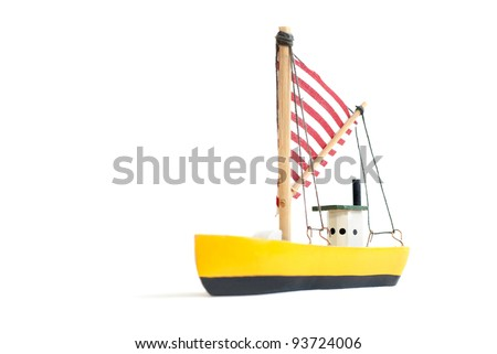 Small yellow toy sailing boat on white background - stock photo