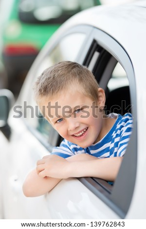 Small young boy in the car smiling and looking out the window - stock photo