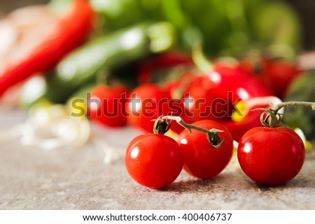 small zucchini with tomatoes and chili salt on a stone background - stock photo