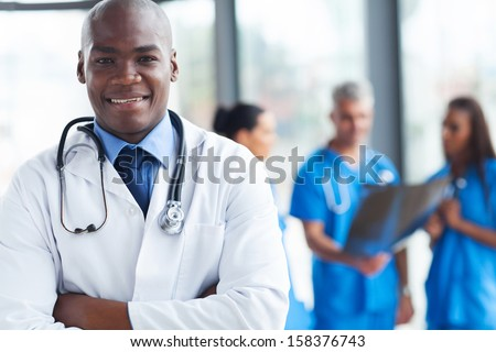 smart african medical surgeon with arms crossed - stock photo