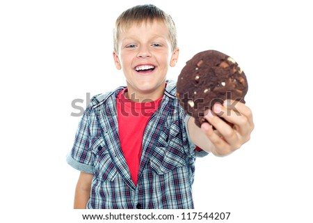 Smart and cheerful boy offering you a chocolate cookie. His arm is outstretched - stock photo
