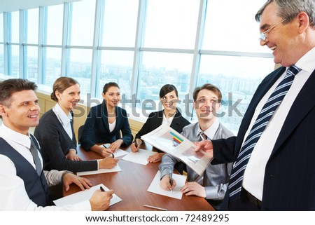 Smart and confident boss looking at managers with papers at meeting - stock photo
