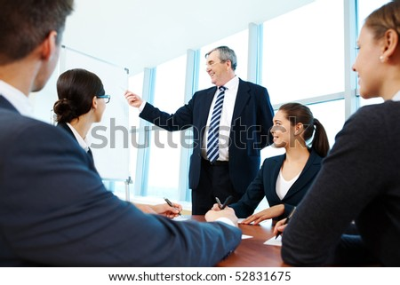 Smart and confident boss pointing at whiteboard while group of employees listening to him - stock photo