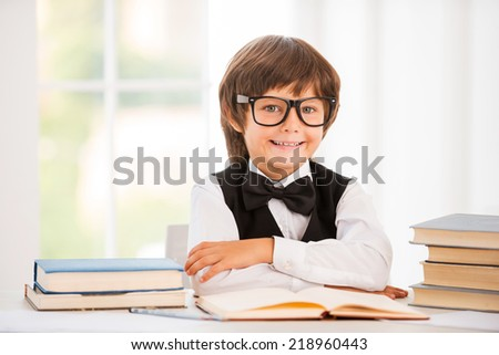 Smart and confident schoolboy. Cute young boy keeping arms crossed while sitting at the table - stock photo