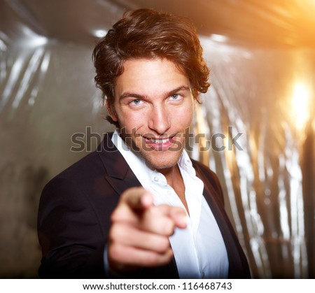 smart attractive businessman points his finger on you - stock photo