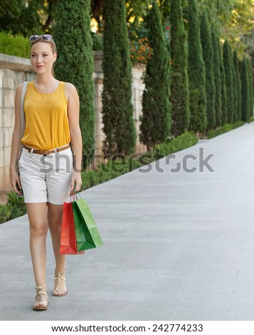 Smart beautiful tourist woman walking by a spacious green park in a destination city, smiling and carrying shopping bags. Young girl consumer lifestyle. - stock photo