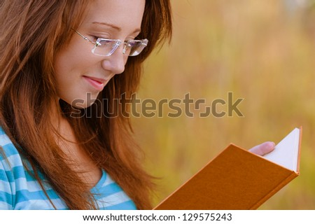 Smart beautiful young woman with glasses reading orange book, against background of summer park. - stock photo