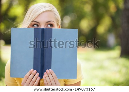 Smart beauty. Beautiful young women holding book in front of her face and looking out of it while relaxing in park - stock photo