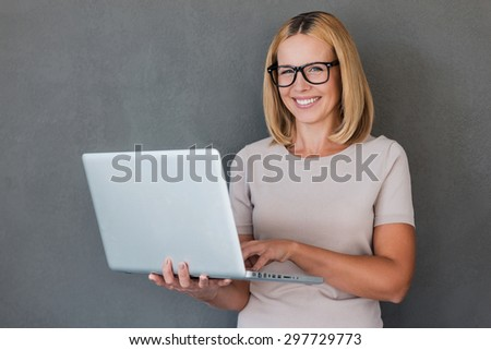 Smart beauty. Smiling mature woman holding laptop and looking at camera while standing against grey background - stock photo