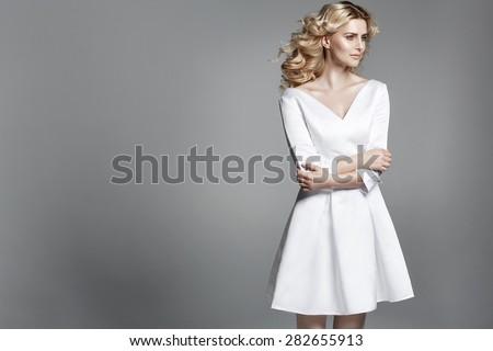 Smart blond lady wearing white dress - stock photo