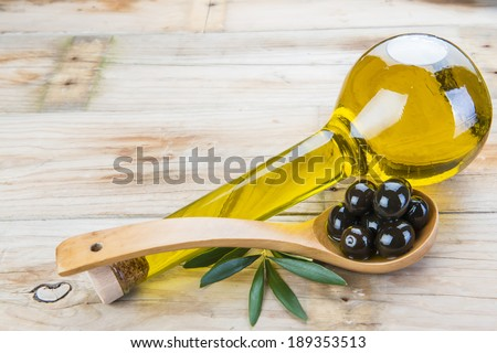 Smart bottle of olive oil and wooden spoon with black olives - stock photo