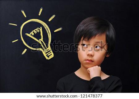 Smart boy in front of blackboard with lightbulb ( eureka / idea concept ) - stock photo