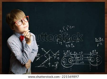 Smart boy in red glasses near blackboard with formulas - stock photo