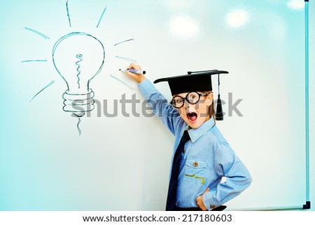 Smart boy stands by the whiteboard in a classroom expressing new idea. Educational concept. Copy space. - stock photo