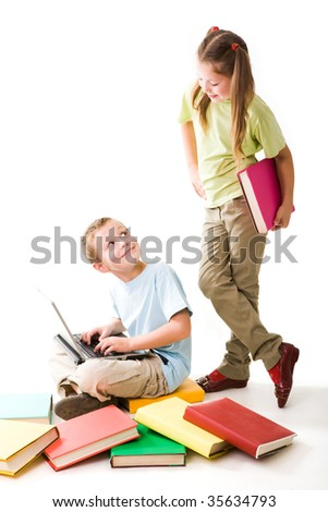 Smart boy typing on laptop and looking at clever girl that standing near by - stock photo