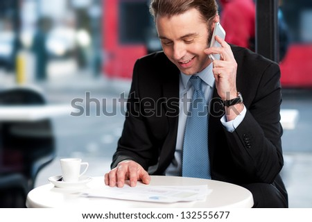 Smart business professional reading menu while in conversation with his colleague. - stock photo