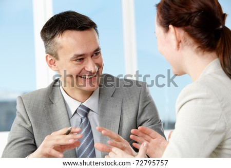 Smart businessman and his colleague interacting in office - stock photo
