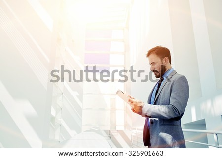 Smart businessman dressed in luxury suit holding touch pad while standing in modern office space with big copy space area for your text message, young intelligent male using digital tablet for work - stock photo