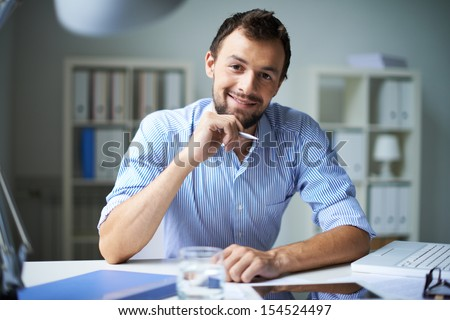 Smart businessman looking at camera with smile in office - stock photo