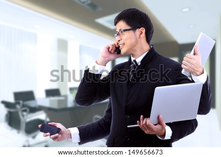 Smart businessman on busy with use many hand hold Electronic commucation tool for check and work in the office - stock photo