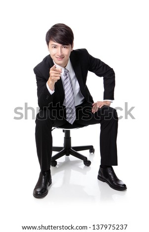 Smart businessman smiling and pointing to you while sitting in full length isolated on white background, asian model - stock photo
