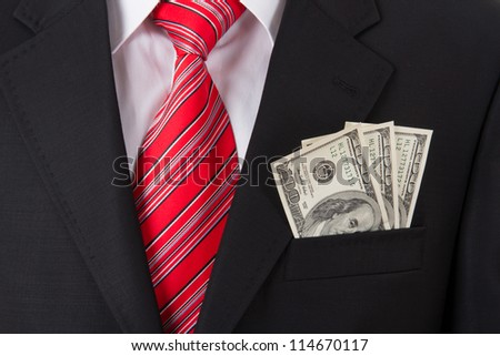 Smart businessman with earned money in suit pocket. - stock photo
