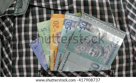 Smart businessman with earned money in suit pocket - stock photo